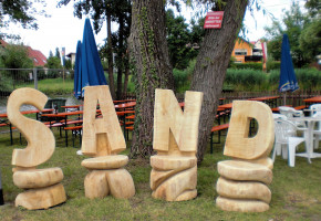 Eine künstlerische Arbeit sind die aus Baumstämmen herausgearbeiteten Buchstaben, die zusammen den Namen S A N D ergeben.