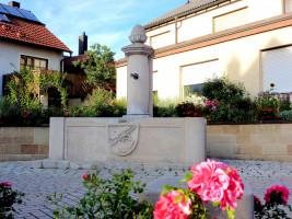 Inmitten des Ortes Sand präsentiert sich der Dorfbrunnen mit dem Gemeindewappen.