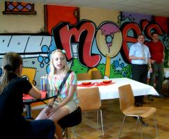 "Der Schriftzug ""Moe`s und Szenen der Simpsons ziert eine Wand des neuen Sander Jugendtreffs. Rechts 1. Bürgermeister Bernhard Ruß im Gespräch mit 3. Bürgermeister Paul Hümmer."