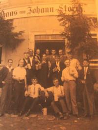 """Das Bild aus früheren Tagen zeigt eine Burschengesellschaft für dem heutigen Gasthaus """"Zum Schiff""""."""